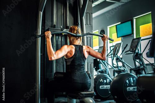 Fototapeta premium Kobieta trenująca na siłowni, mięśnie pleców.