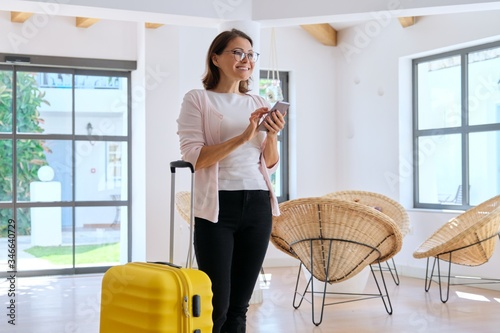 Fotografiet Woman tourist hotel guest with suitcase in lobby of hotel using smartphone