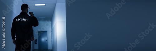 Canvas-taulu Security Guard With Flashlight In Building Corridor
