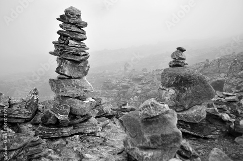 Leinwand Poster Stack Of Cairns On Landscape Against Sky