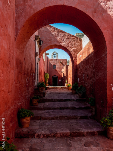 Red painted passage in the Monasterio de Santa Catalina. Long stairs lined with plants in flower pots, run up to a door with a bell tower on top. upright image.