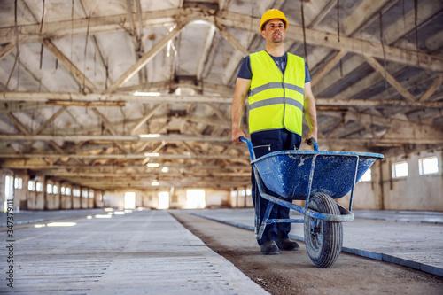 Carta da parati Full length of construction worker pushing wheelbarrow full of cement