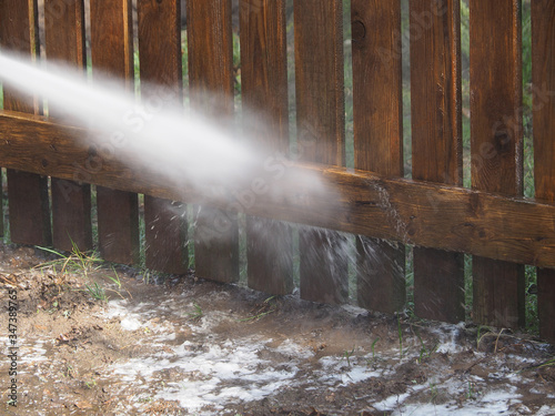 Valokuva Sanitary cleaning private territory and wooden fence with equipment, containing