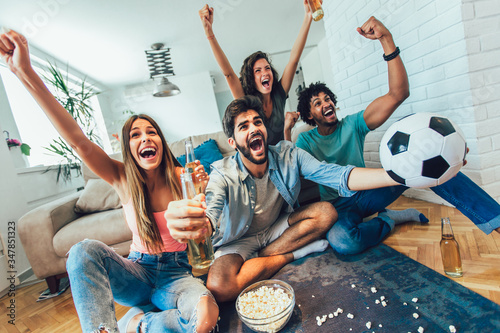 Photo Very excited friends having fun by watching football match and eating at home, indoors