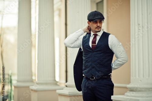 Photo Portrait of retro 1920s english arabian business man wearing dark suit, tie and flat cap
