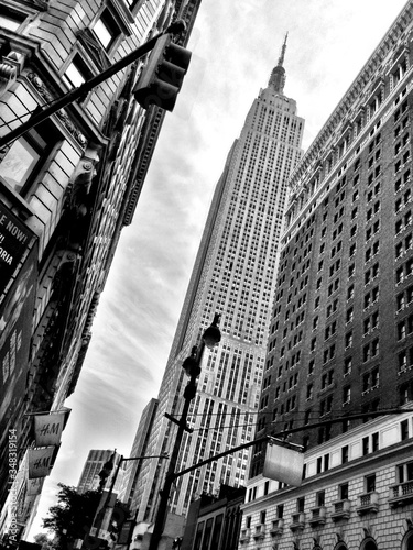 Fotografering Low Angle View Of Empire State Building In City Against Sky