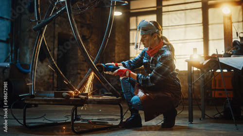 Fotografia Young Contemporary Female Artist is Polishing a Metal Tube Sculpture with an Angle Grinder in a Workshop