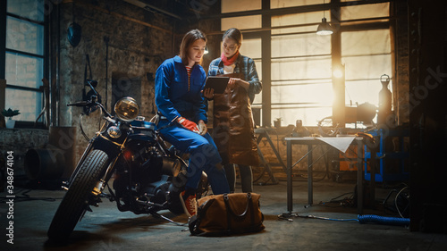 Two Young Beautiful Female are Discussing The Work Done on a Custom Bobber Motorcycle. Talented Girls Use a Tablet Computer. They are In Good Spirit and Happy. Creative Authentic Workshop Garage.
