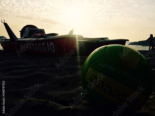 Volleyball And Boat On Sand At Beach Against Sunset Sky