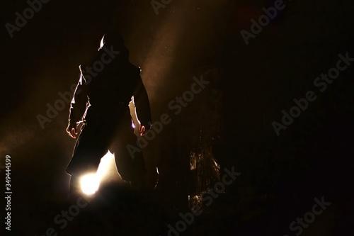 Photo Man In Ninja Costume Standing Against Spot Light