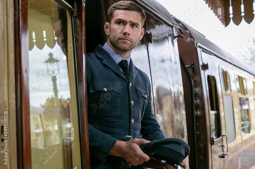 Fotomural Handsome male British officer in vintage uniform at train station, leaving train