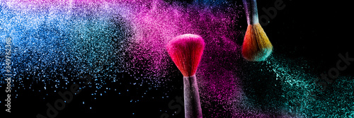 Two brushes with pink and blue make up powder impact to make a colorful cloud.