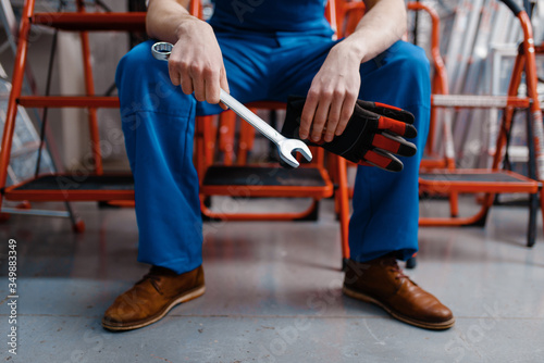Photo Male employee in uniform holds wrench, tool store