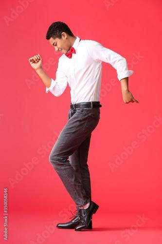 Fotografia African-American teenager dancing against color background