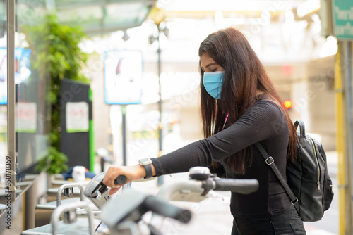Fototapeta Profile view of young Indian woman with mask riding bike at public bicycle servi