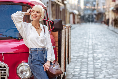 Murais de parede Street style photo of happy smiling fashionable woman wearing trendy white blouse, high waist jeans, with brown faux croco leather textured shoulder bag
