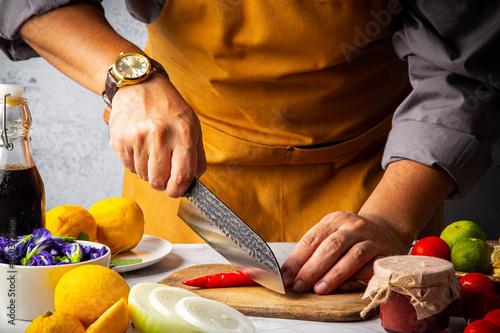 Fotografie, Obraz Male slicing chilli pepper on wooden cutting board by Japanese kitchen damaskus