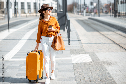 Fotografia Woman with a suitcase on the city street