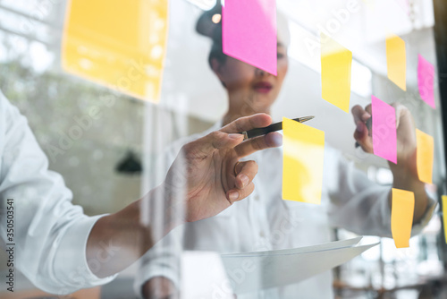 Fotografia Young creative team professional using post it notes in glass wall to writing st