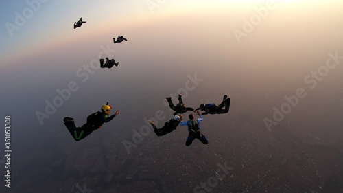 Silhouette of a group of skydivers jumping at the end of the day.