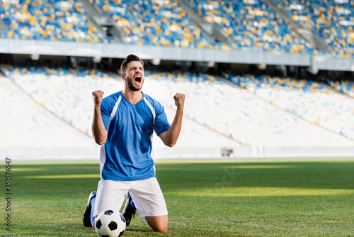 Wallpaper Mural emotional professional soccer player in blue and white uniform with ball standin