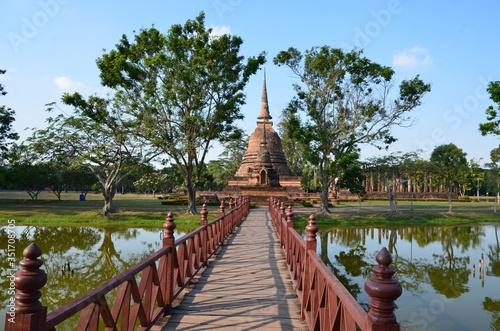 Fotografia A red bridge is leading to Wat Sra Sri, a beautiful temple in the historical par