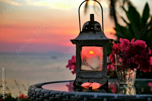 Canvas Print Lantern With Bougainvillea On Table During Sunset