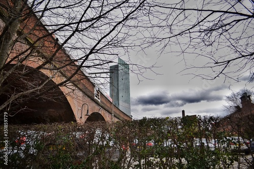 Fotografering Low Angle View Of Arch Bridge By Beetham Tower In City Against Sky