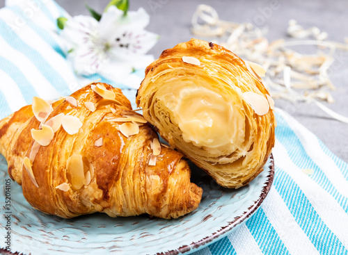Leinwand Poster Yummy freshly golden croissant, sliced almonds, with custard filling cut, close