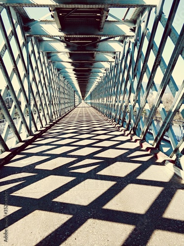 Fotografiet Shadows On Covered Footbridge In City