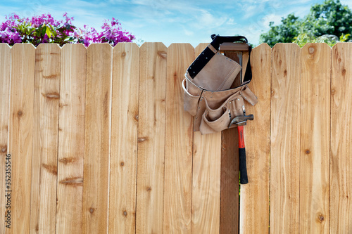 Valokuvatapetti New wooden fence with tool belt and pouch hanging from main post