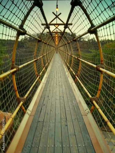 Tablou Canvas Wooden Footbridge In Forest During Sunset