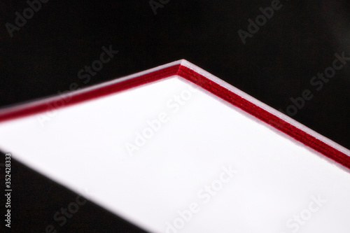 Fotografia White and red three-ply thick stock business cards, floating on a black backgrou