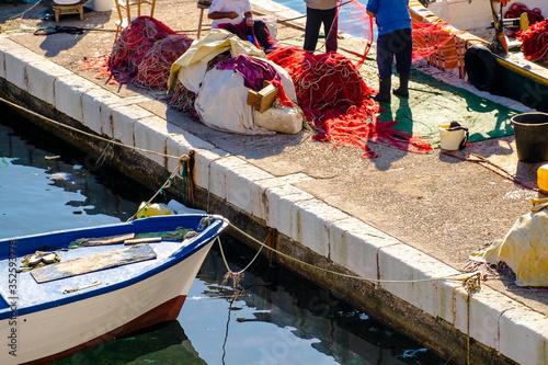 Obraz na płótnie High Angle View Of Fishermen Standing By Fishing Nets On Pier At Harbor