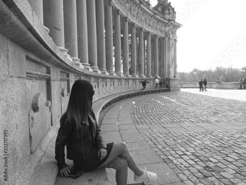 Leinwand Poster Young Woman Sitting By Colonnades At Buen Retiro Park