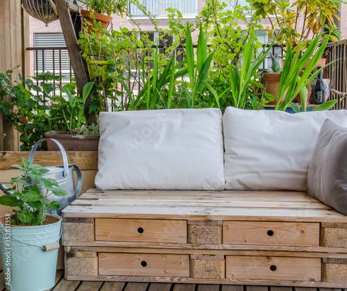 Billede på lærred Wooden pallet couch on balcony with plants in background
