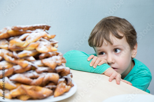 The child looks sadly at the plate with cookies waiting for us to drink tea Fototapeta