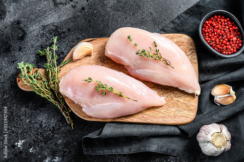 Canvas Print Raw chicken breast fillet on a chopping Board with herbs and spices