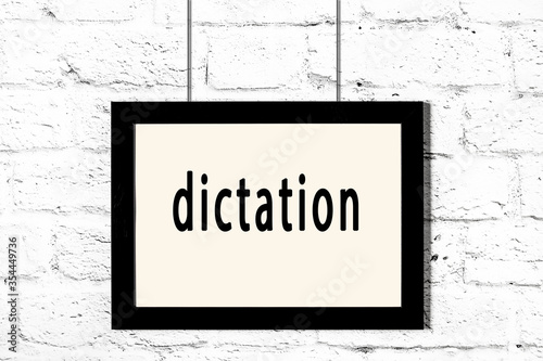 Black frame hanging on white brick wall with inscription dictation Fototapeta