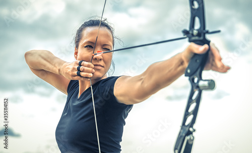 Photo attractive woman on archery, focuses eye target for arrow from bow