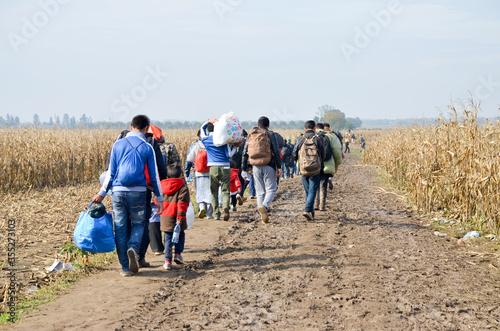 Valokuvatapetti Refugees and migrants walking on fields