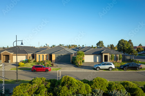 Fotografie, Obraz Elevated view of modern suburban homes in an Australian suburb with family cars parked on side of the street