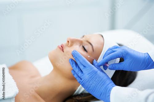 Obraz na plátne Beautiful young woman getting polydioxanone thread lifting at beauty salon