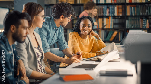Foto University Library: Diverse Group of Gifted Students Have Discussion, use Laptop, Prepare for Exams Together, Helping, Researching Subjects for Paper Assignment