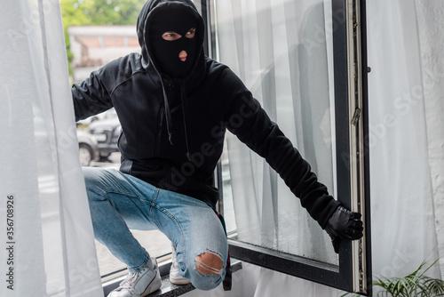 Selective focus of robber in balaclava standing on open window Fototapet