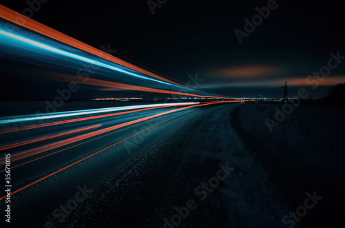Canvas Print Long exposure of a road with light trails of passing vehicles, glowing sky