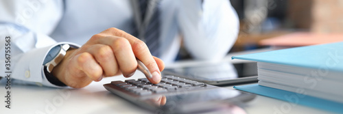 Fotografering Hand of male businessperson making calculations