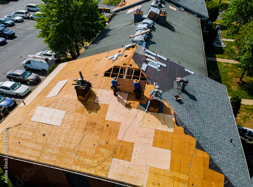 Canvas Print Construction worker on renovation roof the house installed new shingles