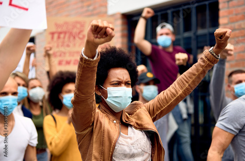 Photographie African American woman wearing protective face mask while protesting with arms raised on city streets