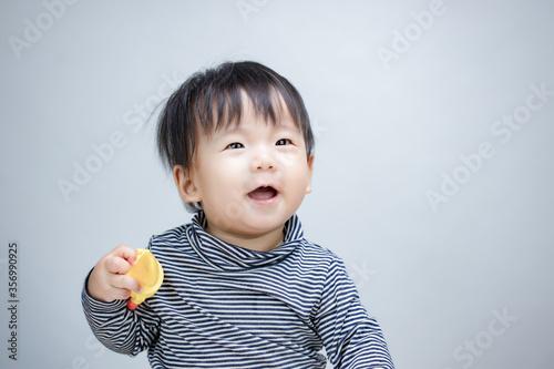 Fotografia Adorable little baby with feeder silicone fruit orange